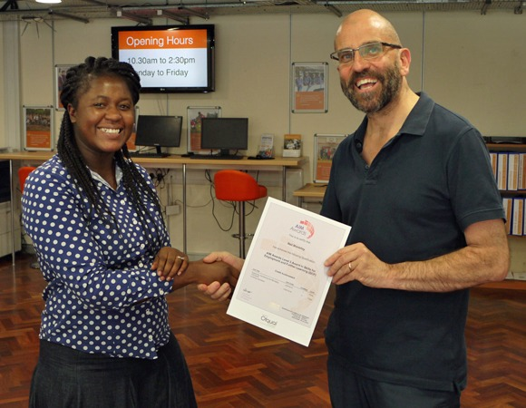 A VAL training participant being handed her certificate for completing her course