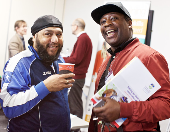 Two-men-attending-a-VAL-funding-fair-and-smiling-at-the-camera