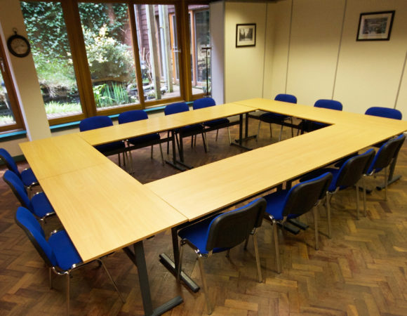 A picture of a meeting room, with tables set out in a large square and blue chairs