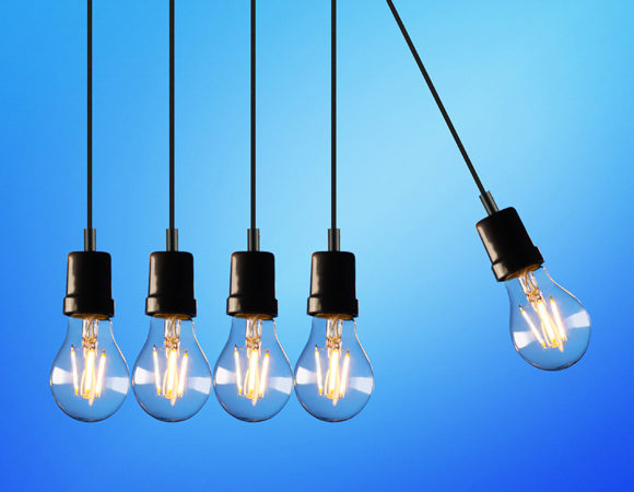 Image of 5 lit hanging lightbulbs against a blue background