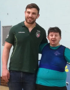 A person with learning disabilities posing with Leicester Tigers player Harry Wells