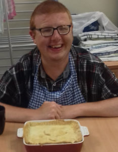 A person with learning disabilities smiling at a table with a pie they cooked