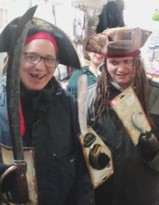 Two people with learning disabilities smiling and posing in pirate costumes