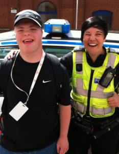 A person with learning disabilities smiling with a police officer in front of a police car
