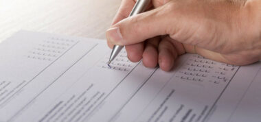 A hand filling in a questionnaire with a pen