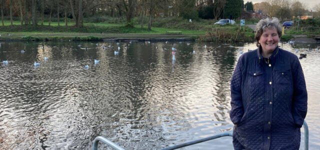 Zoe smiling and standing in front of a river full of ducks