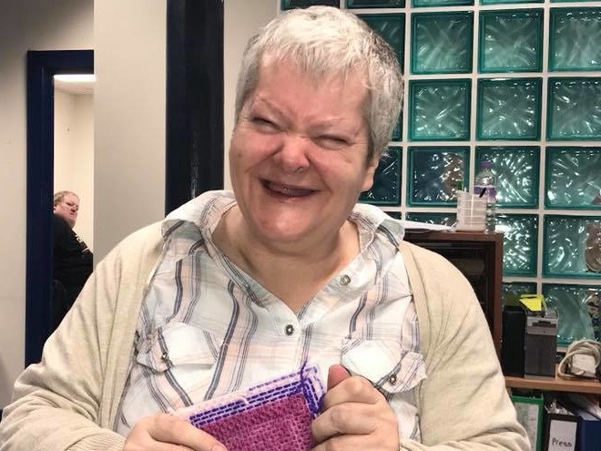 A person with learning disabilities smiling and holding a piece of decorated fabric