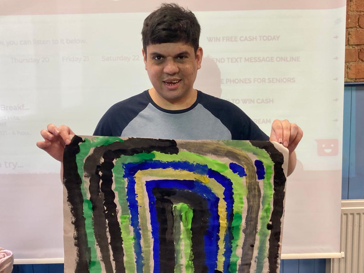 A person with learning disabilities holds a picture of a rainbow that he painted